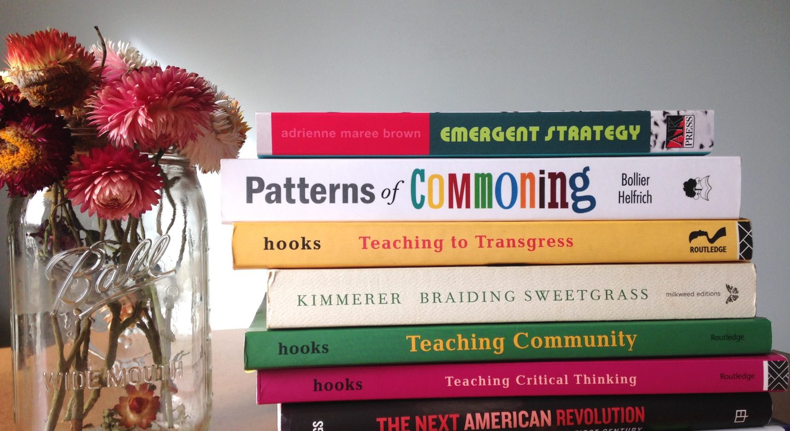 stack of books with jar of straw flowers