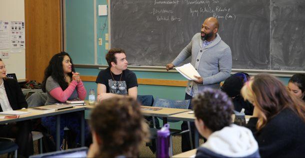 professor talks to class with blackboard