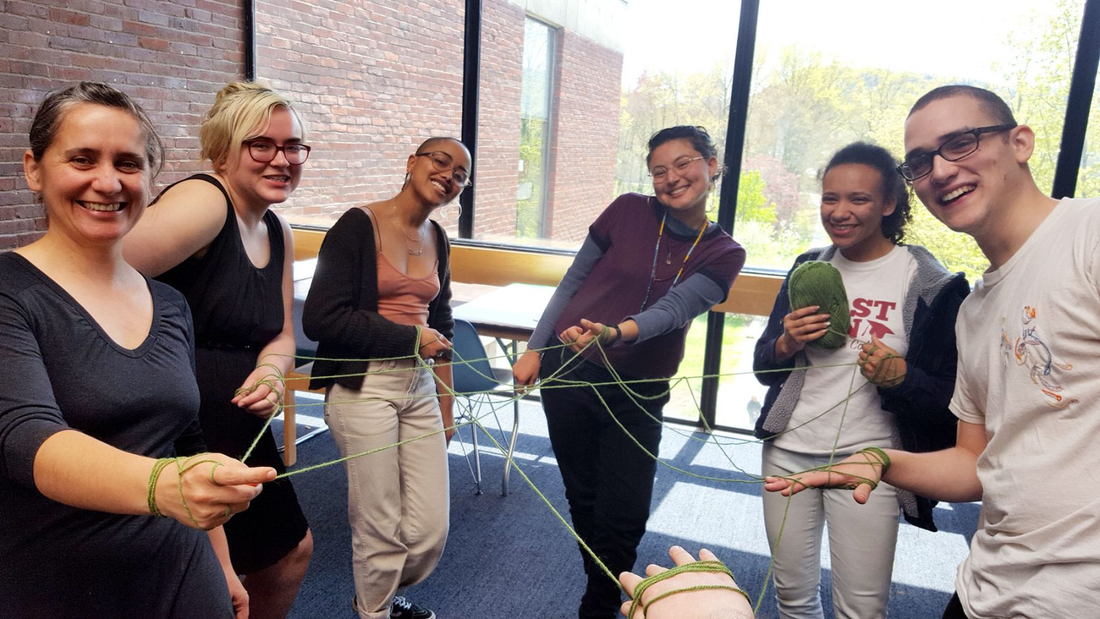smiling circle of people with hands connected by string web