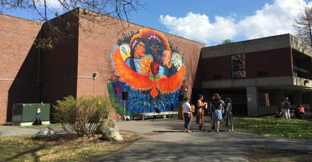 group of people talk under large colorful mural