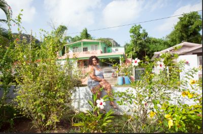 self portrait of carmen sitting on wall in backyard garden of family home in Puerto Rico