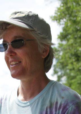 Nancy Hanson in field harvesting veggies