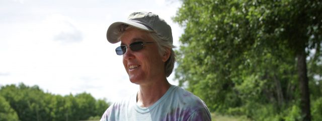 Nancy Hanson in field harvesting veggies