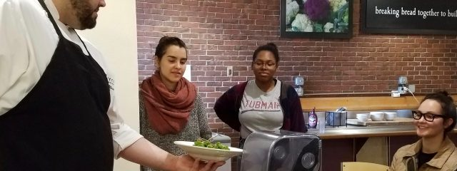 Chef showing plated food to 3 students