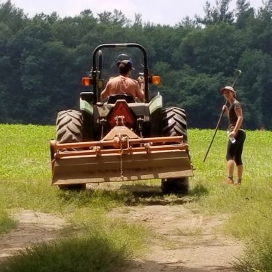 farmer on tractor next to student with hoe