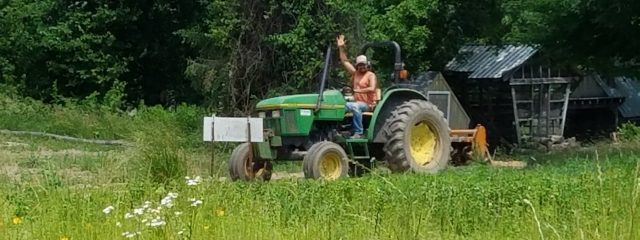Farmer waving from tractor