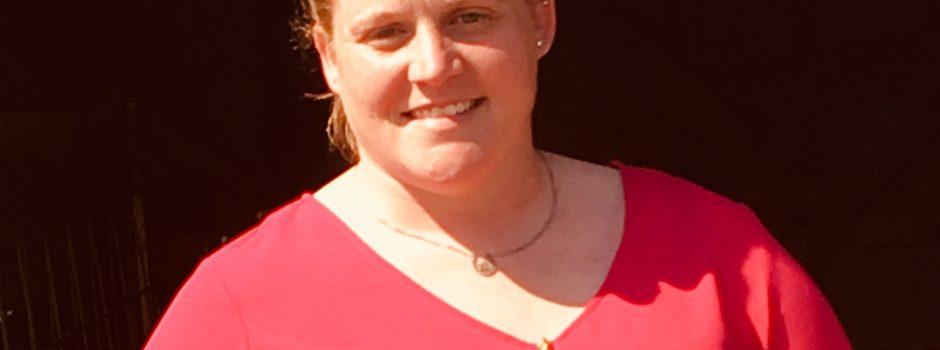 headshot woman red shirt red hair