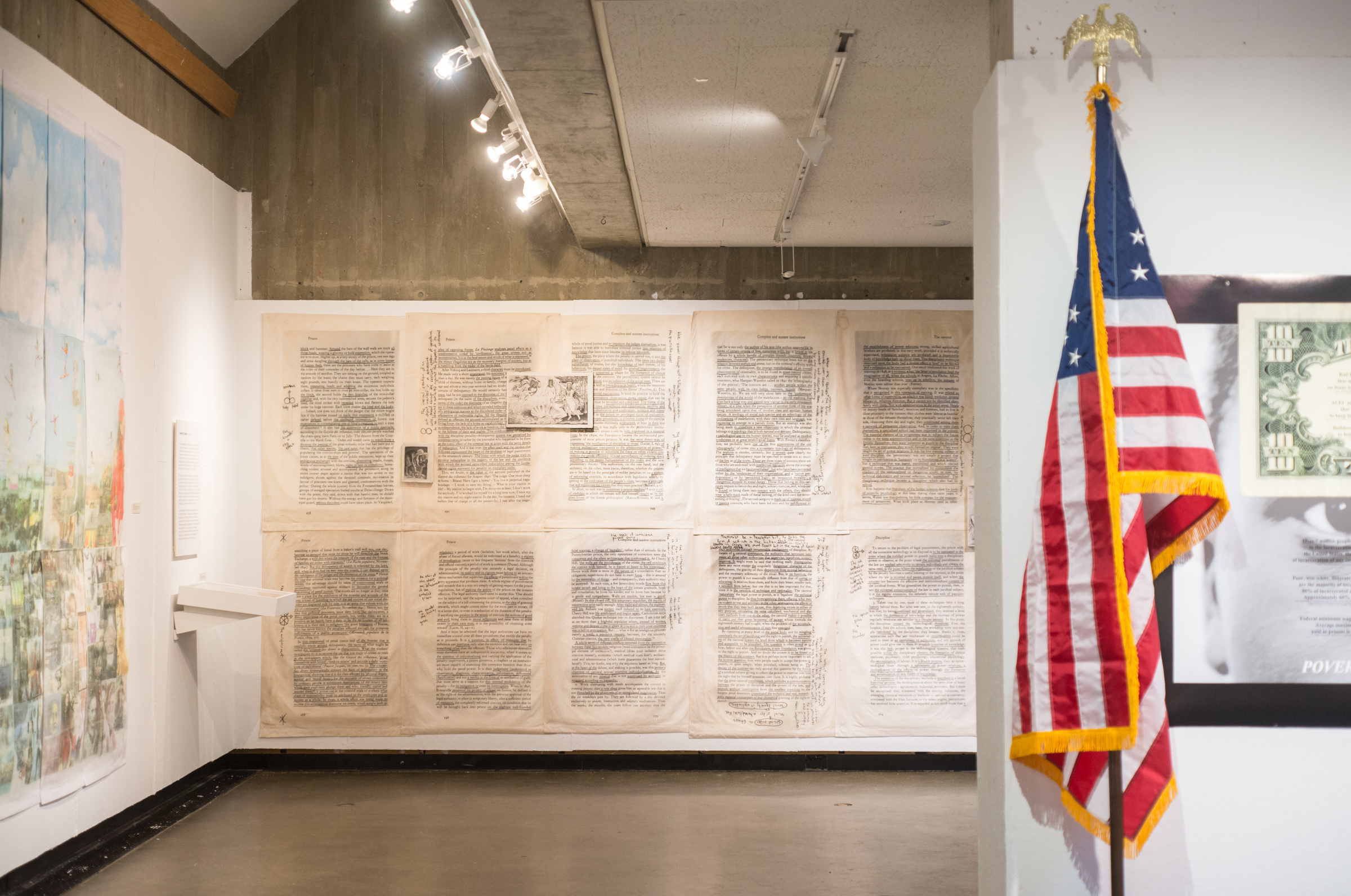 photograph of two gallery walls, one with blown up fabric prints of annotated book pages, and an american flag against another gallery wall