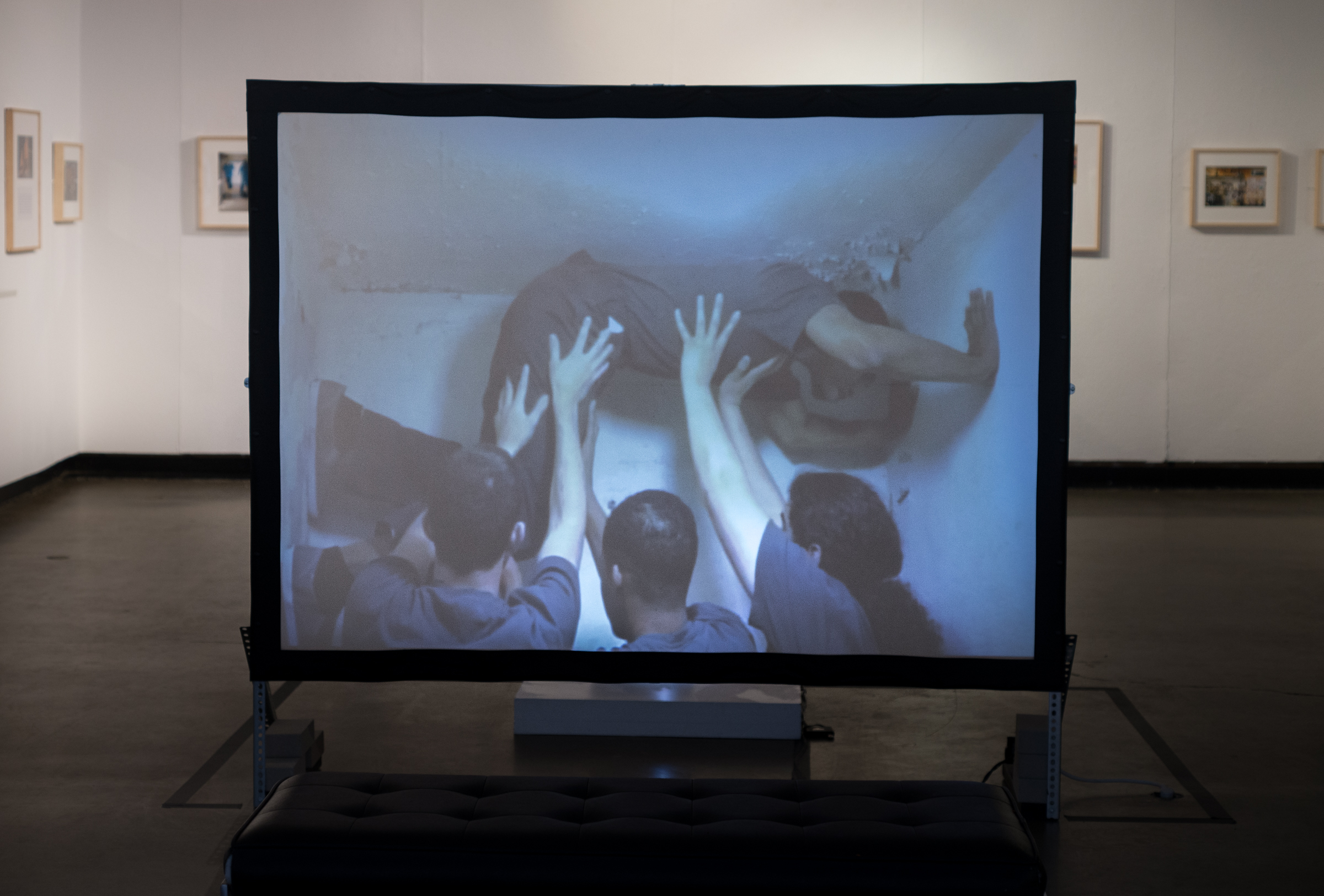 video installation still of dancers in a cell