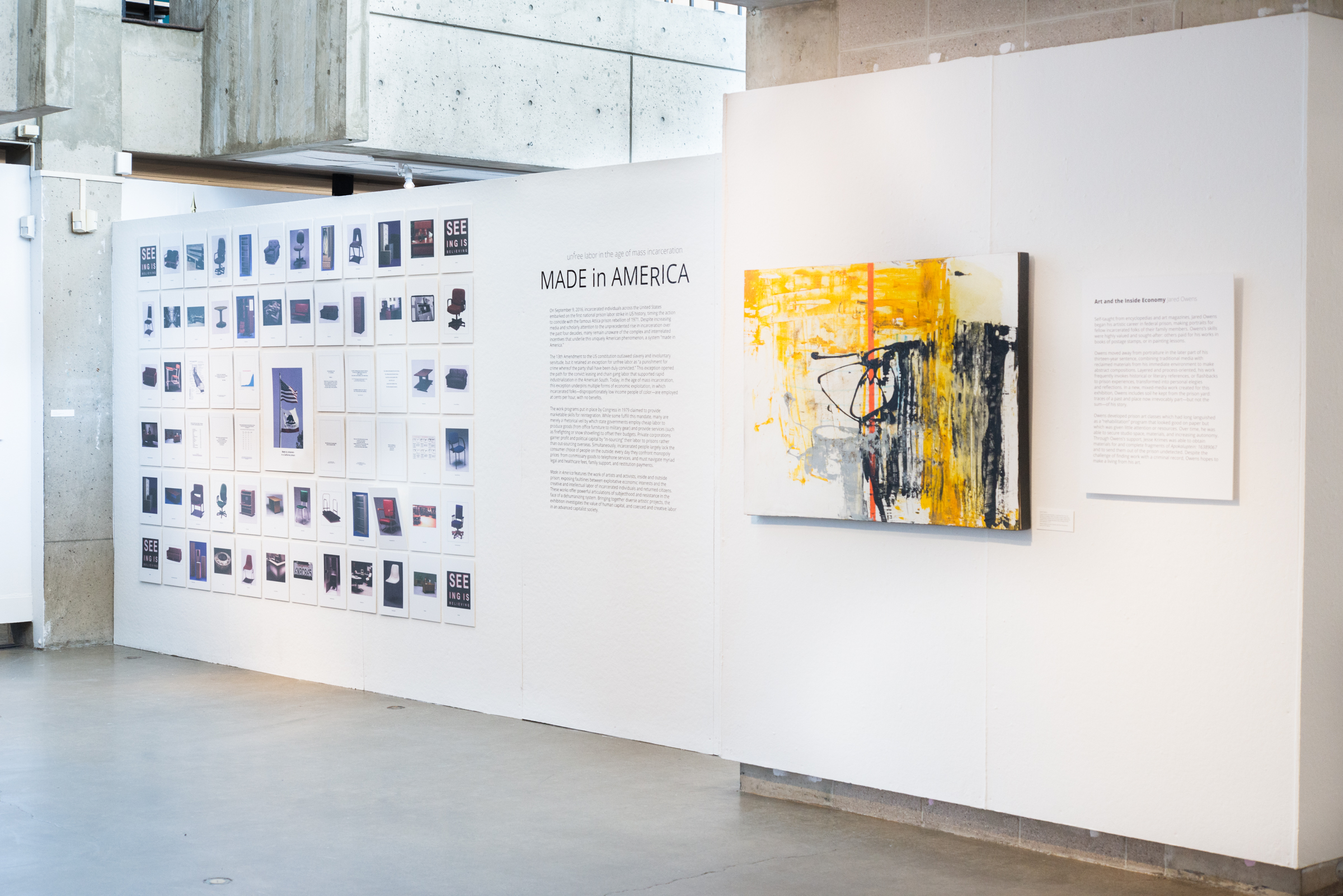 gallery wall with wall of images of products made by United States prisoners, the exhibition title and information, and a large abstract painting