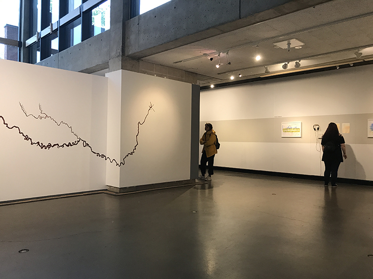 Installation view: Mississippie River laid on its side and series of prints