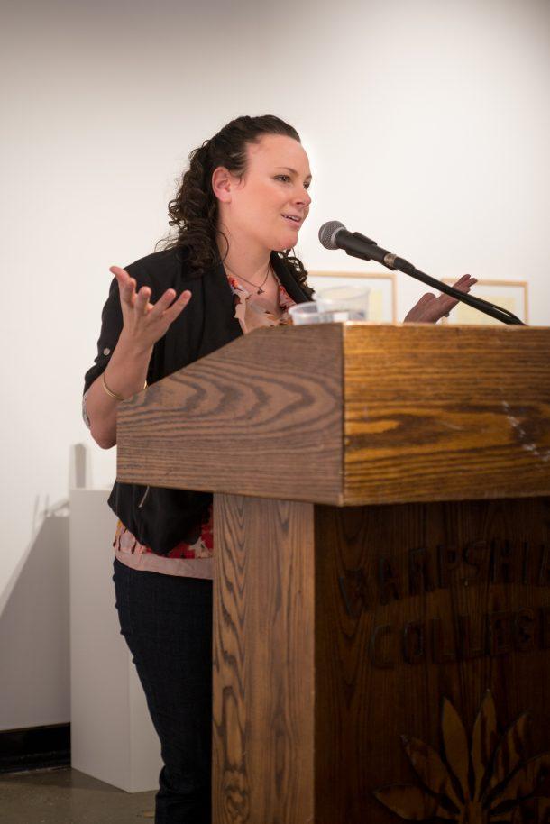 Professor Megan Dobro speaking behind podium