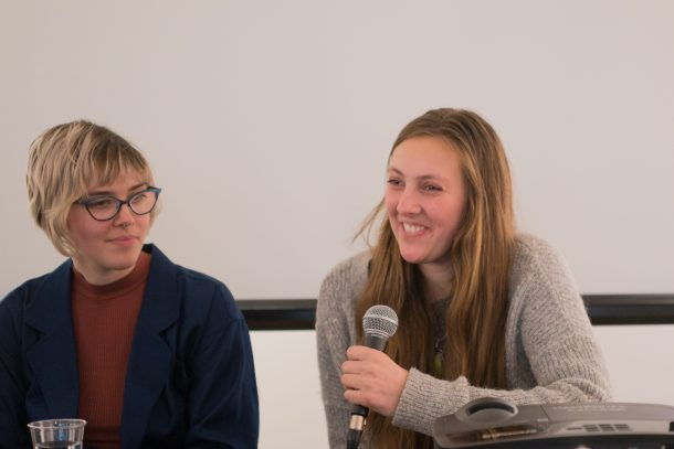 two student panelists, one holding microphone