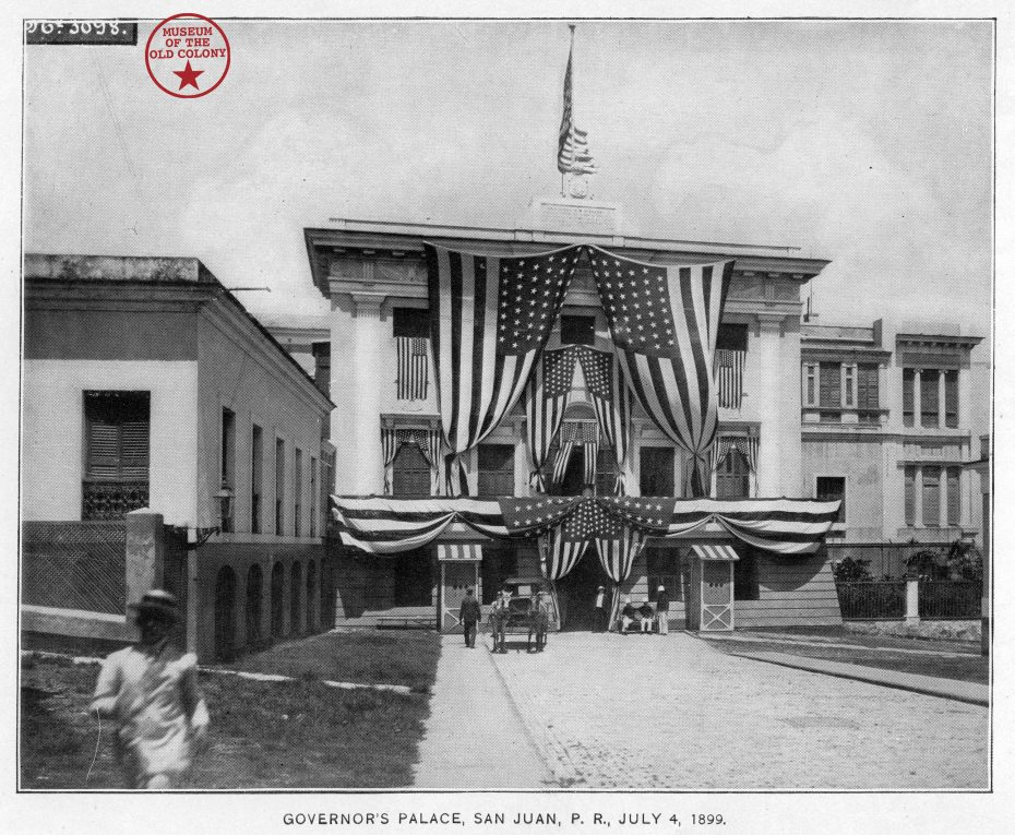 archival image of building decked out in U.S. flags