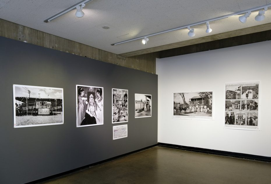 installation shot of two walls in the Gallery with archival black and white photos hung on them