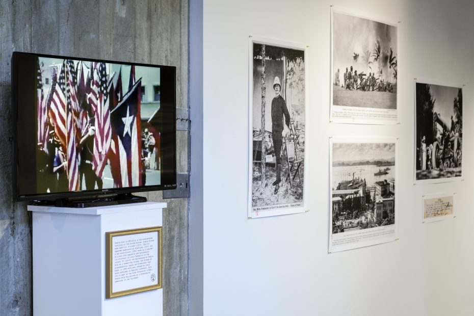 Installation shot of monitor on pedestal with archival propaganda film clip, archival photographs