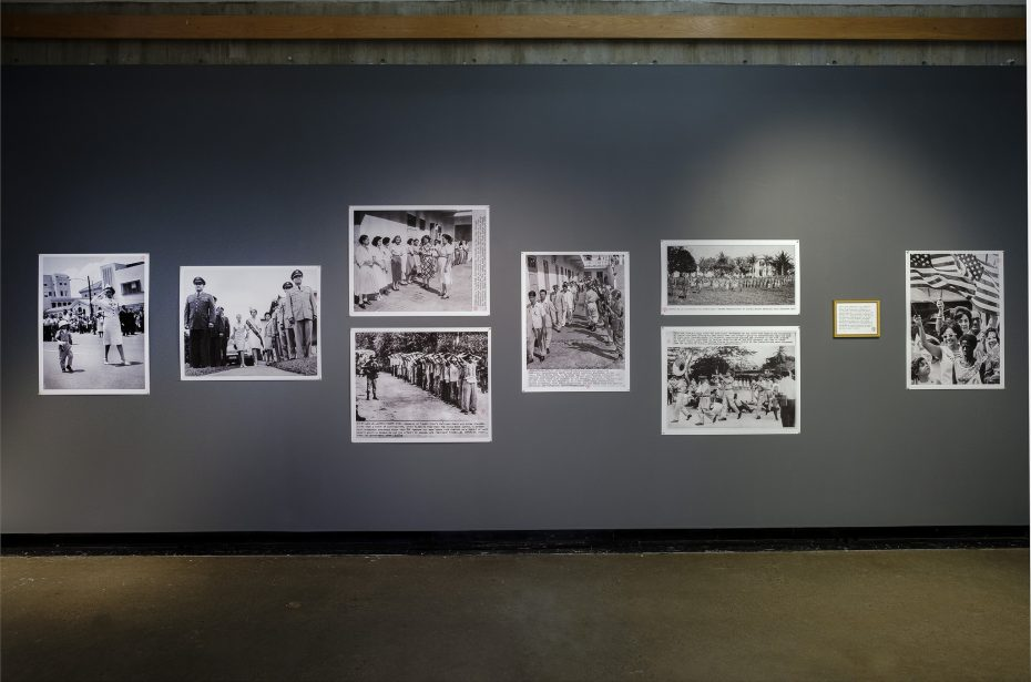 installation shot of one wall of the exhibition. Black and white archival photographs on a dark gray wall