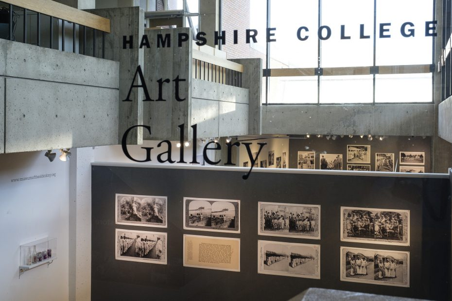 "view from outside the gallery, looking in at the exhibition. Text reads ""Hampshire College Art Gallery"""