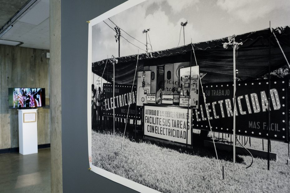 archival photograph of electricity advertising display, tv showing archival propaganda clip in background of photograph