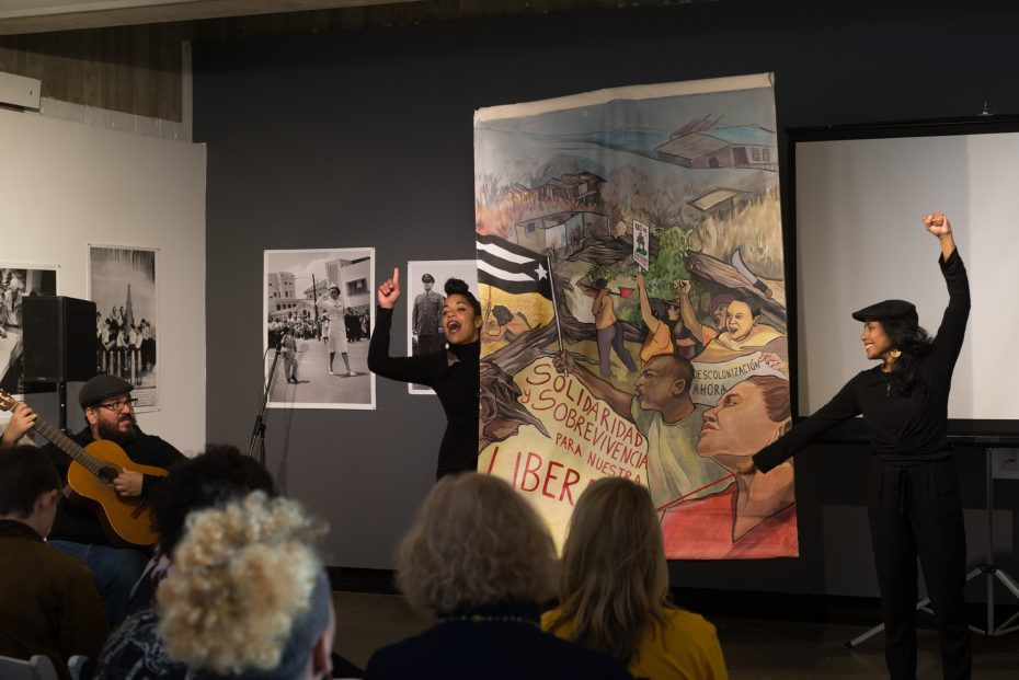 Sugeily Rodríguez Lebrón, & Dey Hernández presenting a Cantastoria with a large painting. Dey is speaking with a finger raised, and Sugeily holds up her fist in solidarity
