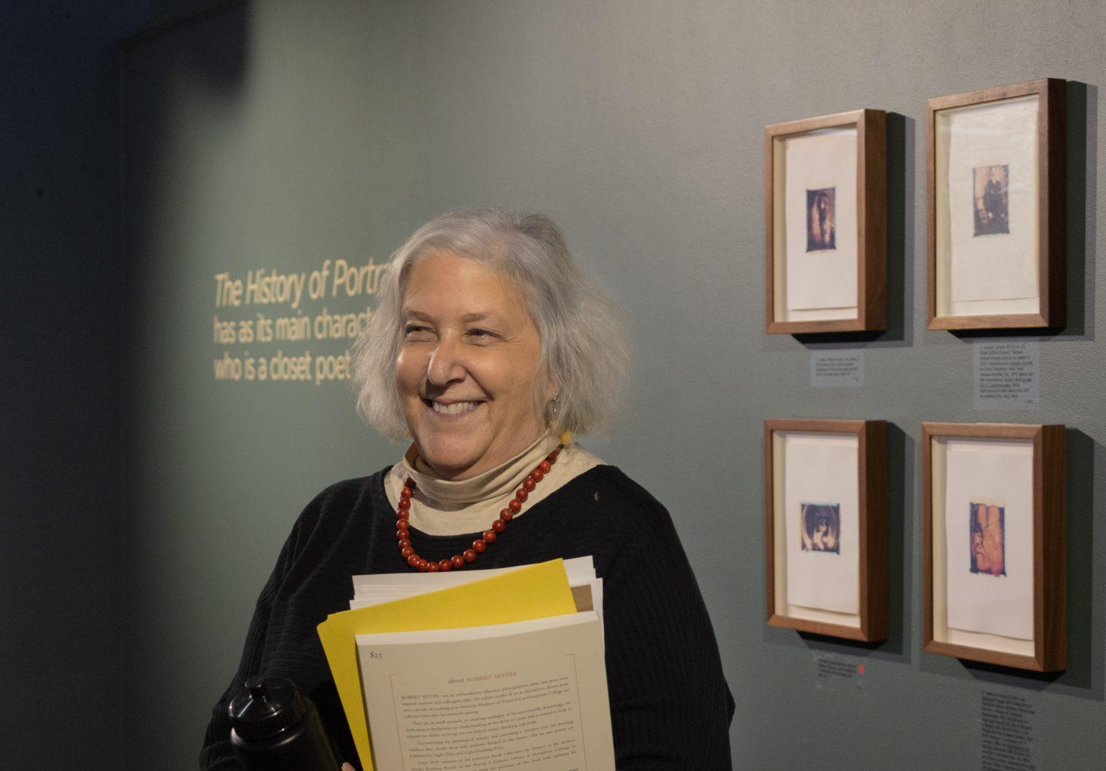 Sura Levine smiling in front of Seydel artworks