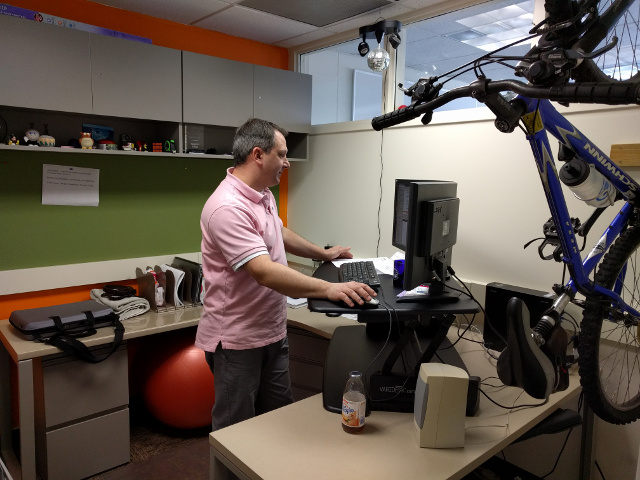 Employee working at a standing desk with a mountain bike hanging next to him