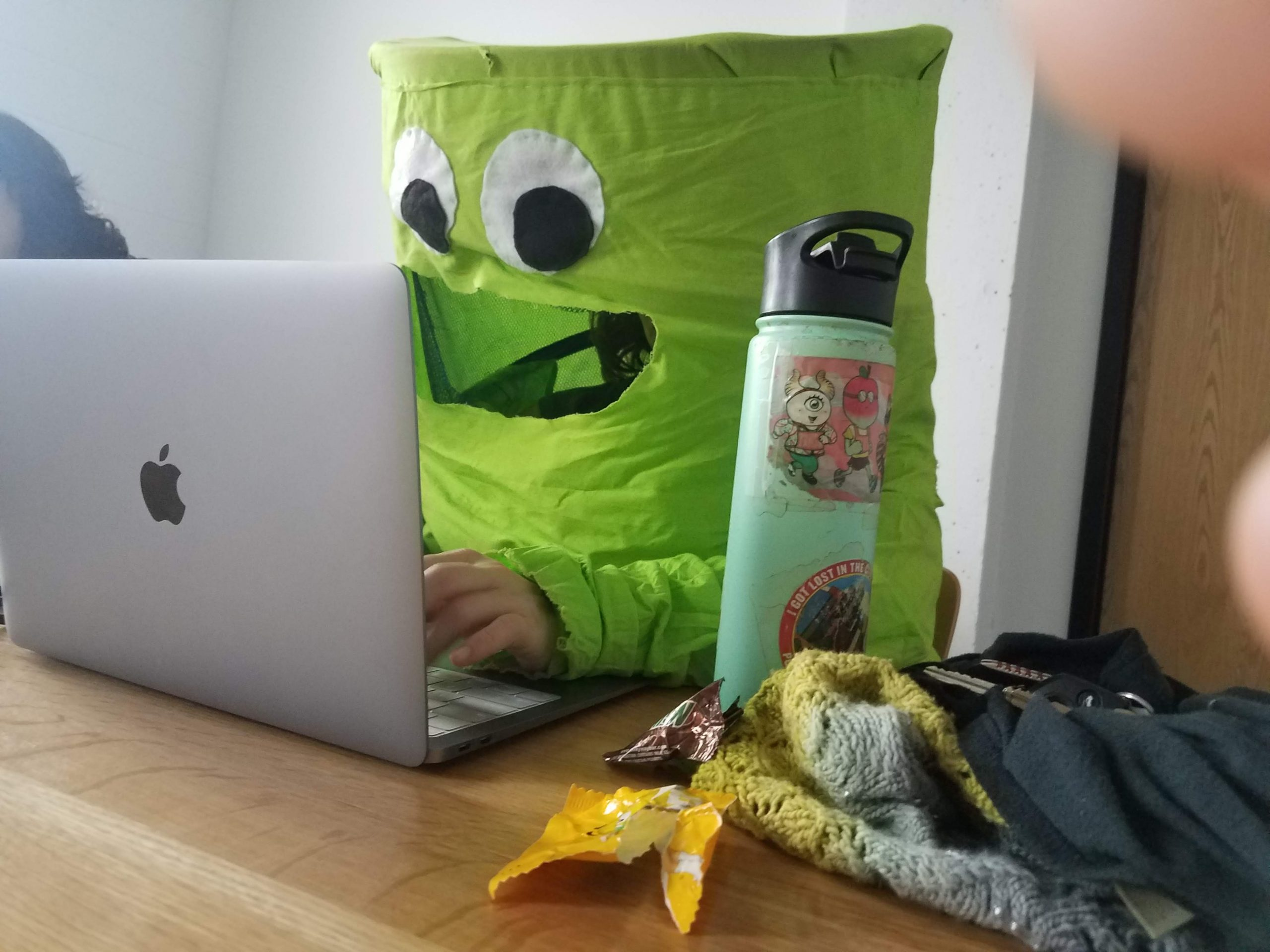 IT staff person wearing googly eye costume and working on laptop