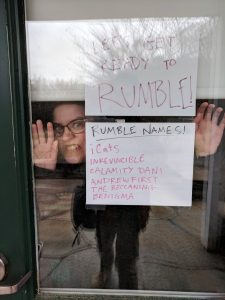 """Sign on door that says """"Let's get ready to rumble!"""" with IT staff person behind it. Additional sign lists Rumble Names: iCats, Inkevincible, Calamity Dani, Andrewfirst, The Beccaning, Benigma"""