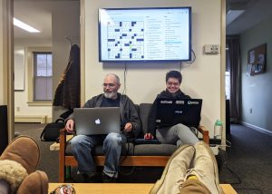Two IT staff working on laptops with a crossword puzzle on a large screen behind them
