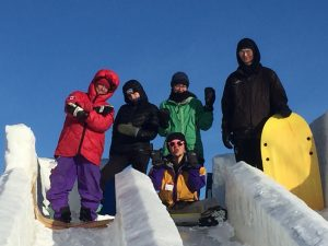 Students posing for a photo while sledding