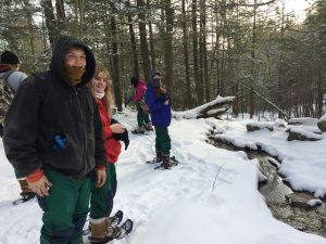 Students snowshoeing near a stream