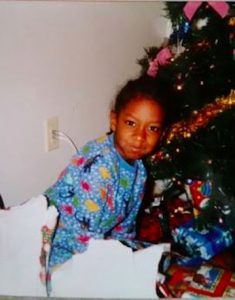 Dawaun as a young child sitting near a Christmas tree