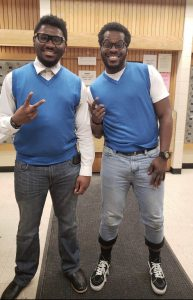 Two men dressed in matching blue vests for twins day