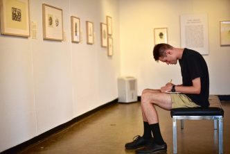 Nolan Boomer, Art Gallery Summer Intern, looks over the Barry Moser exhibit of the lower level of the Harold F. Johnson Library building on the campus of Hampshire College Tuesday, July 5, 2016 in Amherst.