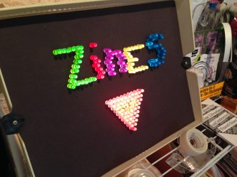 "Lite-Brite board displaying the word ""Zines"" and a pink triangle, on display at QZAP."