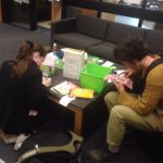 students working on gratitude journals in library