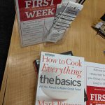 "A photograph of the ""First Week"" poster and a cookbook"
