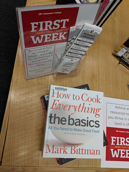 """A photograph of the """"First Week"""" poster and a cookbook"""