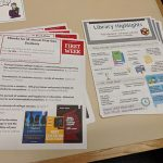 A photograph of two flyers, one containing some ebooks for and about first-gen students, the other presenting some library highlights